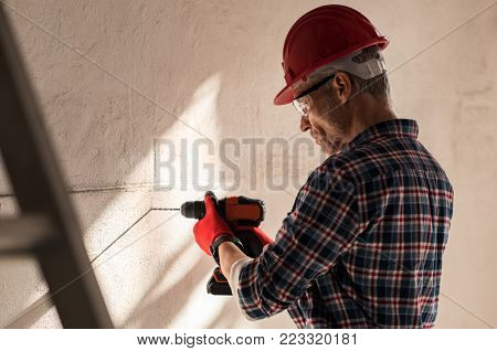 Construction worker making hole in wall with electric drill. Bricklayer drilling hole in wall in a construction site. Mature man wearing hardhat making a hole in wall for maintenance work.