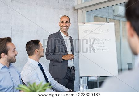 Mature businessman talking about project during meeting in modern office. Senior business man showing strategy plan to his colleagues. Business team having a meeting in boardroom.
