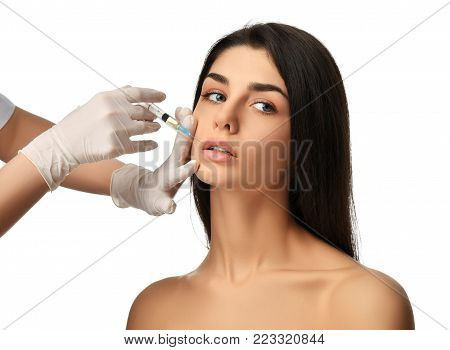 Face cosmetology plastic surgery beauty concept young brunette woman receiving Hyaluronic Acid injection in glove with syringe