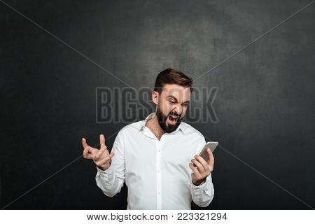 Emotional male worker screaming in anger and outrage while looking on screen of silver smartphone over dark gray background