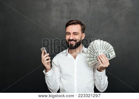 Portrait of cheerful man in white shirt winning lots of money dollar currency using his smartphone being joyful over dark gray background