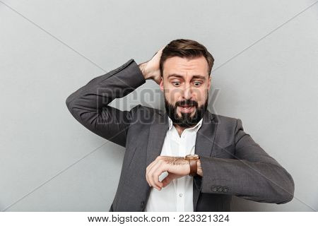Horizontal image of astonished man looking at wrist watch touching his head being late posing isolated over gray background