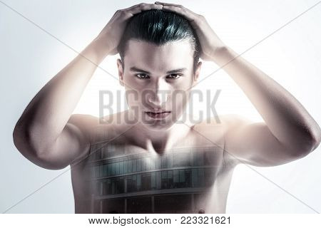Modern businessman. Serious focused earnest guy touching his hair while gazing straight and getting ready