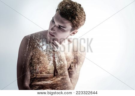 Lonely road. Pensive charming earnest guy  closing eyes while touching face and turning head from the camera