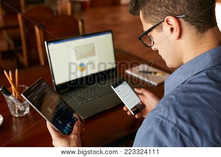 Attractive man in glasses working with multiple electronic devices. Freelancer businessman has laptop and smartphone in hands and laptop on table with charts on screen. Multitasking theme.