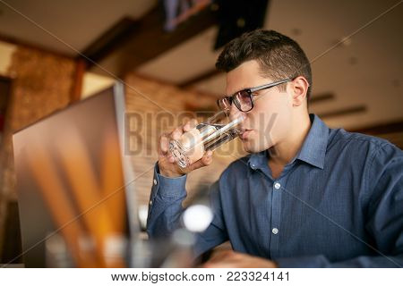 Handsome caucasian man with glass of water in hand works with laptop. Businessman in glasses drinks water for body hydration while working. Attractive designer quench thirst.