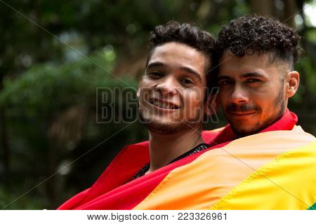 Homosexual Couple Embracing and Looking to the Camera with Rainbow Flag in the Park