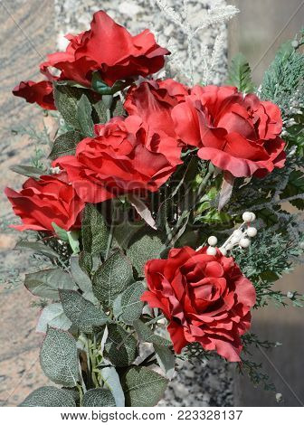 All weather artificial fabric red roses left on grave stone to express love and remembrance