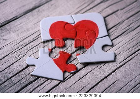 closeup of some separated pieces of a puzzle which together form a heart on a white rustic wooden surface, depicting the idea of rupture or cooperation