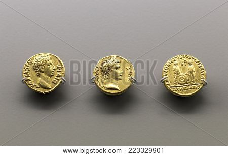 Merida, Spain - December 20th, 2017: Three golden coins of Augustus Emperor at National Museum of Roman Art in Merida, Spain