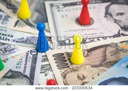 World money game or economic strategy, colorful plastic game figurines on international major countries banknotes, US dollar, Japanese yen, Euro, Chinese yuan.