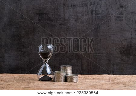 Financial time or long term investment concept with hourglass or sandglass and stack of coins on wooden table with textured black cement wall background and copy space.
