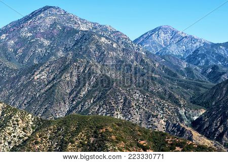 Arid barren landscape including a chaparral woodland with the San Gabriel Mountains beyond taken in Claremont, CA