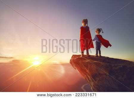 Two little children are playing superhero. Kids on the background of sunset sky. Girl power concept