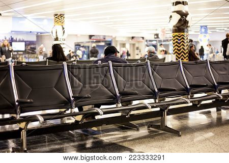 Airport row of seats with people waiting/airport waiting lounge