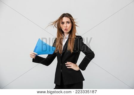 Portrait of a young businesswoman dressed in suit waving with a folder isolated over gray background