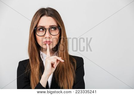 Portrait of a pensive businesswoman dressed in suit thinking and looking away isolated over gray background