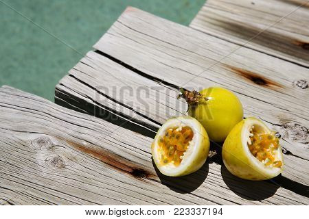 Yellow Passionfruit on wood beside a swimming pool