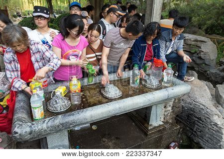 April 2015 - Jinan, China - local people taking water from the springs in the famous Baotu Quan in Jinan, also called the Best Spring in the World .