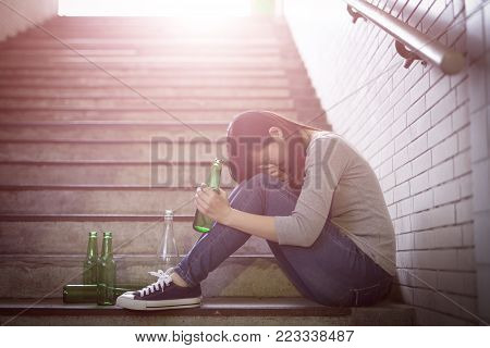 depressed woman feel upset with alcoholism problem and sit in underground