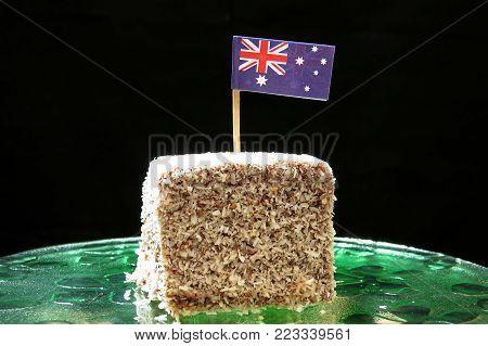 Lamington with Australian flag. Australia Day. True blue Aussie food with chocolate, coconut and sponge cake.