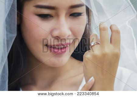 Beautiful bride hand with beautiful diamond ring on white dress at wedding day outdoors at ocean beach.