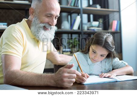 Proud of her. Positive minded elderly gentleman beaming while sitting next to his little grandchild and helping her with home assignment.