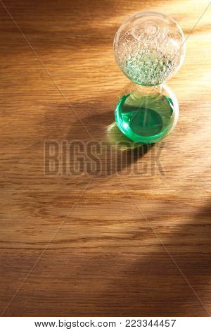liquid type of hour glass on the wooden background