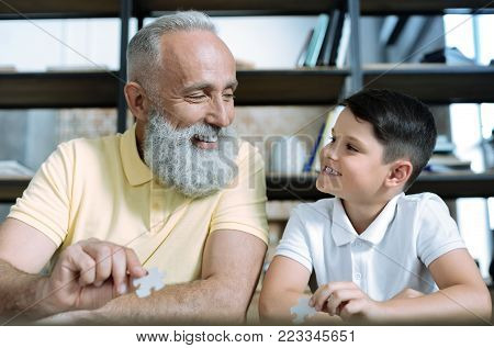 Never bored together. Waist up shot of positive minded retired gentleman and his grandchild looking at each other and grinning broadly while holding puzzle pieces at home.
