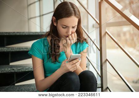 Upset teenage girl with smartphone indoors. Cyber bullying