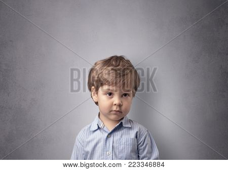 Adorable little boy portrait with empty grey wall background