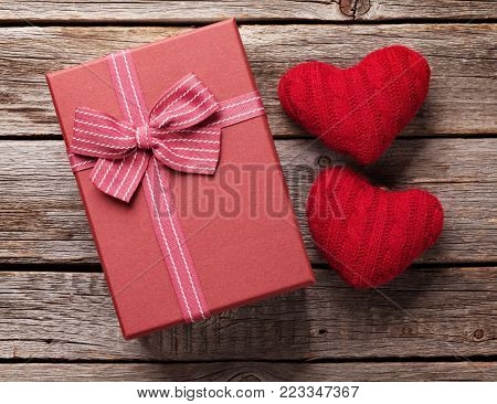 Valentines day gift box and hearts over wooden background. Top view