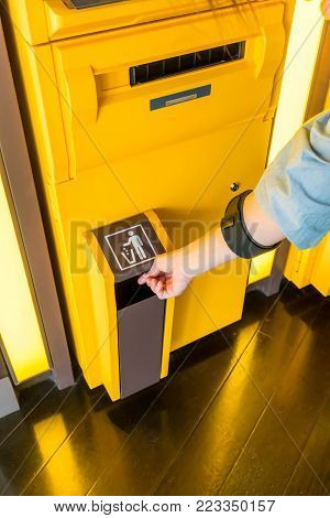 Hand of Asian woman throwing trash into trash box on yellow ATM machine.