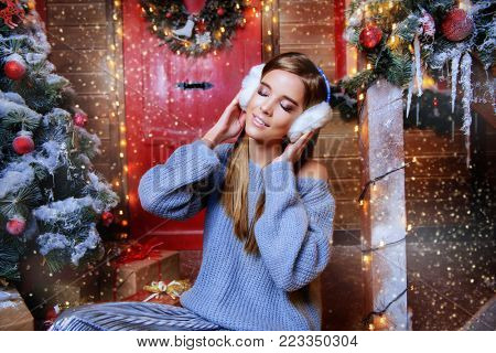 Happy girl in a warm winter clothes and earmuffs poses near the house decorated for Christmas. Time for miracles. Merry Christmas and Happy New Year.
