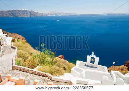 Santorini island, Greece. White bell tower on the coast