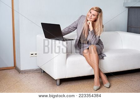 Smiling businesswoman sitting on sofa with laptop computer in office lobby.