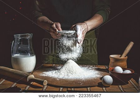 Preparation of bread dough. Bakery, baker's hands, flour is poured, flying flour. toned