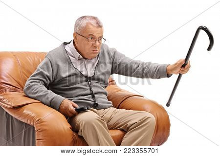 Annoyed senior with a cane sitting in an armchair and watching television isolated on white background