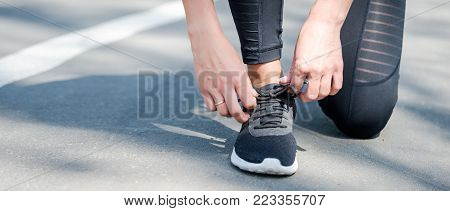 Young beautiful sportive girl preparing to run in the park