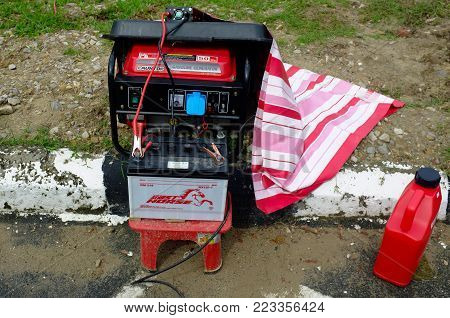 Labuan,Malaysia-Jan 18,2018:Gasoline portable generator with car battery ready for backup in Labuan,Malaysia.Its effective as emergency power supplies in case of a disaster or large-scale power outage & as temporary power sources.