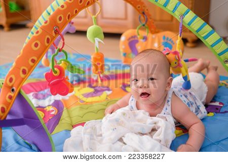 Cute little Asian 5 - 6 months old baby boy child wearing tank top & diaper at tummy time playing toys on play gym on wooden floor in living room at Home at looking in camera - Selective Focus