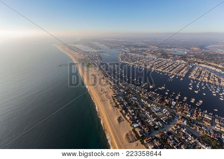Aerial view of Newport Beach bay and harbor with afternoon pacific ocean fog rolling in.