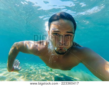 male swimmer under water in the sea makes selfie and let the bubbles of oxygen