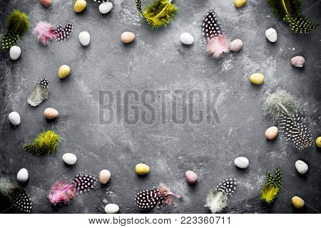 Easter background with mini candy eggs and speckled colorful feather on a dark background top view empty space for text