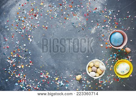 Easter background with painted eggs and colorful crushed eggshell on dark background top view empty space for text
