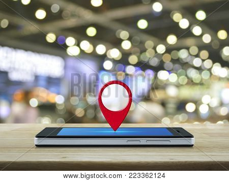 Map pin location button on modern smart phone screen on wooden table over blur light and shadow of mall, Map pointer navigation concept