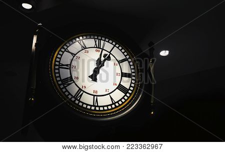 A large clock in the dark with dim light. Watch the clock. Work takes time