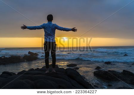 Young man silhouetted open hands and arms at dawn sunrise on the beach standing looking out over ocean waves with rocky coastline landscape