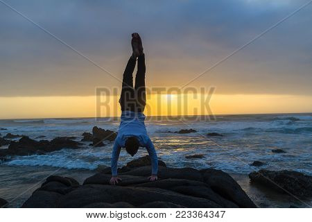 Young man silhouetted handstand on rock at dawn sunrise on the beach ocean waves with rocky coastline landscape
