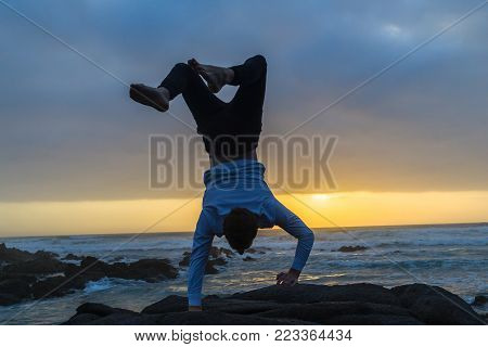 Young man silhouetted handstand on beach rock at dawn sunrise on ocean waves with rocky coastline landscape
